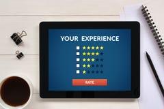顾客在片剂屏幕上的回顾概念有办公室的反对 库存照片