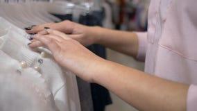 顾客妇女的手选择在挂衣架的新的时髦的衣裳在时尚精品店在销售期间晒干,未聚焦 股票视频