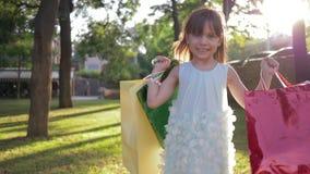 顾客孩子画象有许多的从昂贵的精品店的购买在公园在晴天站立并且微笑 影视素材