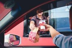 顾客接受汉堡包的和冰淇凌在命令以后和通过服务买它从麦克唐纳` s驱动 库存图片