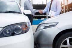 顾客有汽车保险代理的震动手在同意以后 库存图片