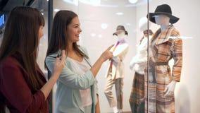 顾客生活方式,快乐的女朋友在商店窗口谈论在时装模特的时兴的新的汇集衣裳  股票视频