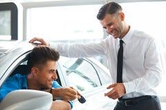 顾客的汽车推销员移交的新的汽车钥匙陈列室的 库存图片