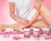 给顾客的腿打蜡的治疗师在温泉 库存图片