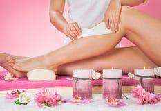 给顾客的腿打蜡的治疗师在温泉 免版税库存图片