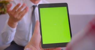 顾客经理特写镜头画象谈话与客户有绿色色度关键屏幕的藏品片剂在办公室 影视素材