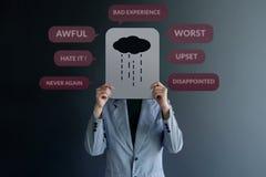 顾客经验概念 Uhappy在墙壁的客户身分有悲伤的标志的在纸的 围拢由否定的评审  库存照片