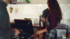 顾客购买在现代咖啡店的外卖咖啡并且支付与付不接触的付款的智能手机 股票视频