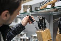 顾客选择套刀子的` s手 免版税库存照片