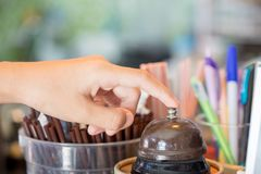 顾客` s手在柜台的紧迫响铃在咖啡店 免版税库存图片