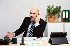 顾问解释演算给电话的顾客 图库摄影