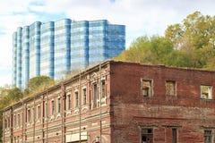 顿河畔罗斯托夫,俄罗斯, 2017年10月07日:在街道上的老被毁坏的大厦在市反对背景的顿河畔罗斯托夫 免版税库存照片