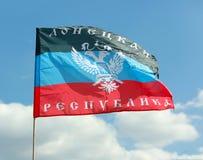 顿涅茨克在天空背景的共和国旗子  免版税库存照片