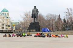 顿涅茨克,乌克兰- 2015年2月, 11日:在离开的中心广场的儿童的乘驾反对纪念碑的背景对Len的 免版税库存照片