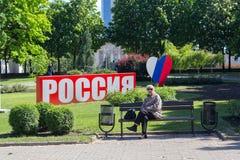 顿涅茨克,乌克兰- 2017年5月17日:妇女在一个公园在市中心以有inscriptio的设施为背景 库存图片
