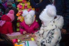 顿涅茨克,乌克兰- 2016年12月23日:孩子在一棵符号树的标签写在列宁广场 库存图片