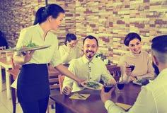 整顿秩序访客的女性侍者在国家餐馆 库存图片