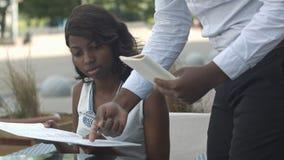预定从菜单在餐馆和决定怎样的美丽的美国黑人的妇女吃 图库摄影