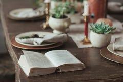 预定说谎在桌上服务与多汁植物,蜡烛,土气板材 读在咖啡馆概念 免版税图库摄影
