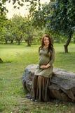 预期婴孩的年轻人孕妇坐一块大石头在公园在阳光下发出光线 图库摄影