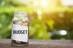 预算与硬币的词在有储款的玻璃瓶子和财政 库存照片