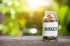 预算与硬币的词在有储款的玻璃瓶子和财政 免版税图库摄影