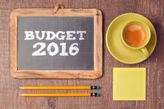 预算的企业概念2016个新年 有咖啡杯的黑板在木书桌上 免版税图库摄影