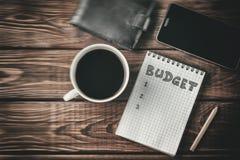 预算飞行的概念 笔记薄顶视图与词预算,手机,杯子的 库存图片