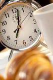 预警早餐时钟咖啡新月形面包 免版税库存图片