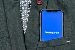 预订 com在苹果计算机iPhone x屏幕特写镜头的应用象在夹克口袋 售票app象 预订 com 社会媒介app 免版税库存图片