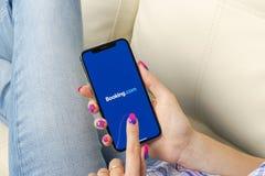 预订 com在苹果计算机iPhone x屏幕特写镜头的应用象在妇女手上 售票app象 预订 com 社会媒介app S 库存照片