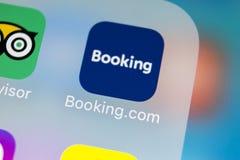 预订 com在苹果计算机iPhone x屏幕特写镜头的应用象 售票app象 预订 com 社会媒介app 3d网络照片回报了社交 库存照片