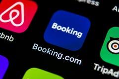 预订 com在苹果计算机iPhone x屏幕特写镜头的应用象 售票app象 预订 com 社会媒介app 3d网络照片回报了社交 图库摄影