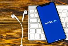 预订 com在苹果计算机iPhone x屏幕特写镜头的应用象 售票app象 预订 com 社会媒介app 3d网络照片回报了社交 免版税库存图片