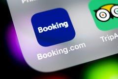 预订 com在苹果计算机iPhone x屏幕特写镜头的应用象 售票app象 预订 com 社会媒介app 3d网络照片回报了社交 免版税图库摄影