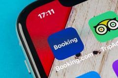 预订 com在苹果计算机iPhone x屏幕特写镜头的应用象 售票app象 预订 com 社会媒介app 3d网络照片回报了社交 免版税库存照片