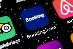 预订 com在苹果计算机iPhone x屏幕特写镜头的应用象 售票app象 预订 com 社会媒介app 3d网络照片回报了社交 库存图片