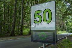 预防雷达,限速检测装置,数字式机敏的标志-它显示绿色愉快的面孔和限速50在街道上 免版税库存照片