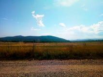 领域、山和天空 免版税库存照片