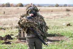 领域伪装的战士与在战斗前的一杆自动步枪 免版税图库摄影
