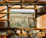 领域和森林的看法通过一辆老生锈的公共汽车的窗口 免版税图库摄影