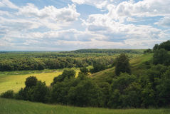 领域和草甸一个多小山谷的在多云夏天天空下 免版税库存照片