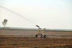 领域的准备耕种的 水一个领域的喷水隆头设施在天旱期间 库存图片