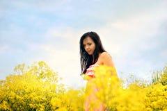 领域的女孩与黄色开花太阳光芒和蓝天 免版税图库摄影
