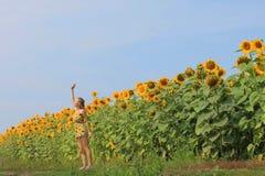 领域的女孩用向日葵 免版税库存图片