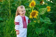 领域的小女孩用向日葵 免版税库存照片