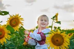 领域的小女孩用向日葵 免版税库存图片
