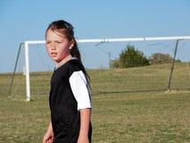 领域的年轻足球女孩在比赛期间 免版税库存照片