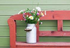 领域花花束在葡萄酒牛奶罐头的 免版税库存照片