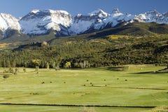 领域,对多雪的山峰的山麓小丘 免版税库存照片